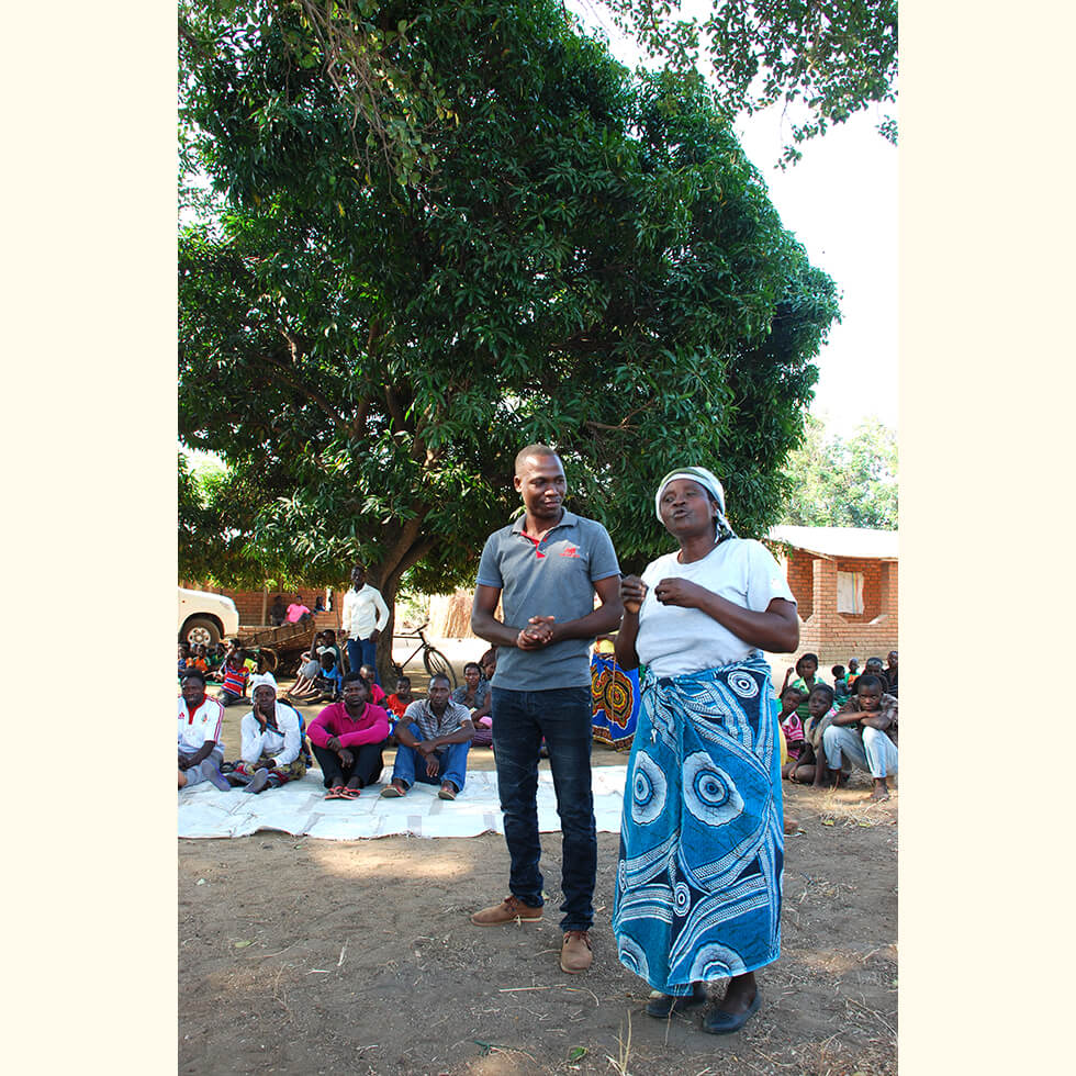 A village Head reports to a District meeting the success of the Village Fish Conservation Committee's (volunteers) work in protecting their area from illegal fishing activity