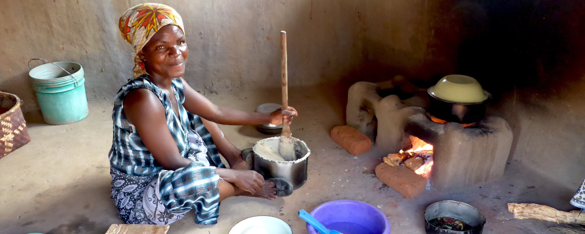 A woman cooks lunch on her Changu Changu moto fuel efficient cookstove in Malawi