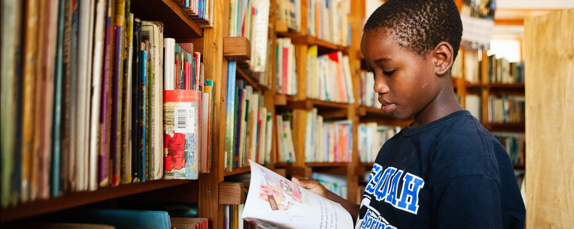 A child selects a book to read in a community library in Africa