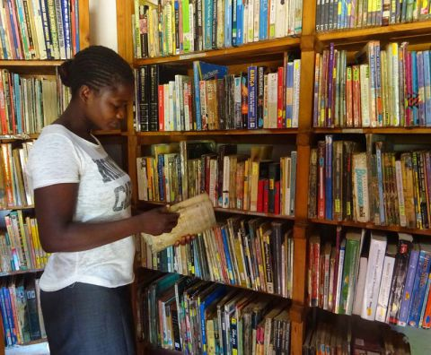 A reader chooses a book at a community library in Malawi