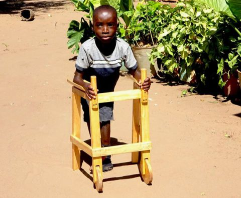 A spina bifida client walks with the help of a walking frame in Africa