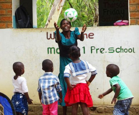 A preschool teacher plays catch with her pupils in Malawi