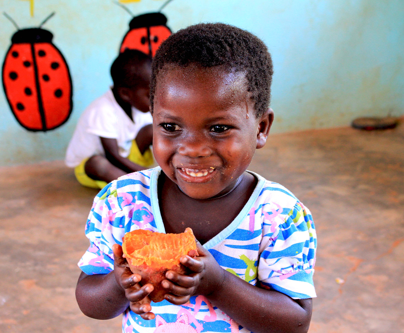 A child eating sweet potato at a Ripple Africa in Malawi