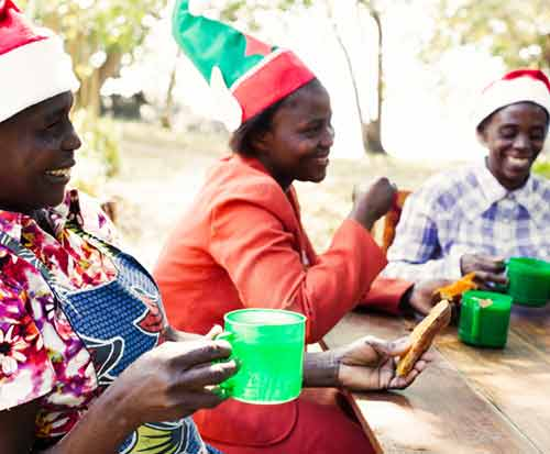 Ladies in Malawi drink tea while wearing Christmas hats