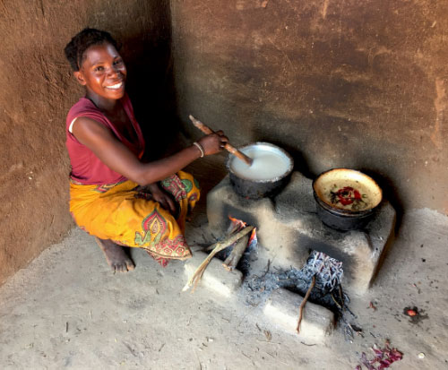 Lady cooking on a fuel-efficient cookstoveLady cooking on a fuel efficient cookstove in Malawi