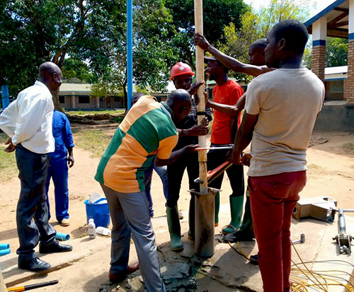 Maintenance team repair a broken borehole in Malawi to provide clean water in Africa