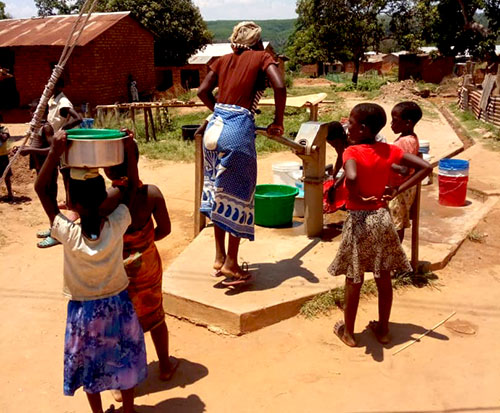 A woman pumps clean water in Africa at a working borehole