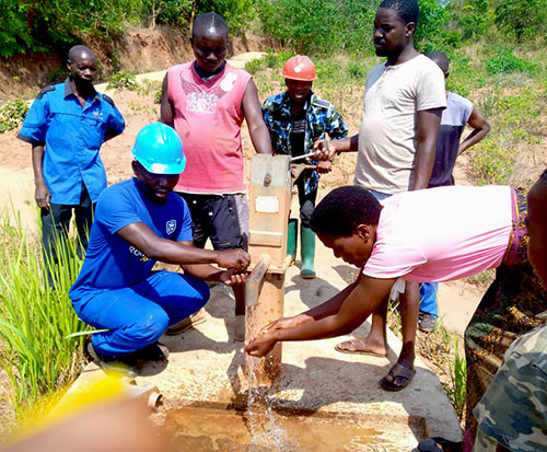 Maintenance men check the water is pumping from a borehole in Malawi