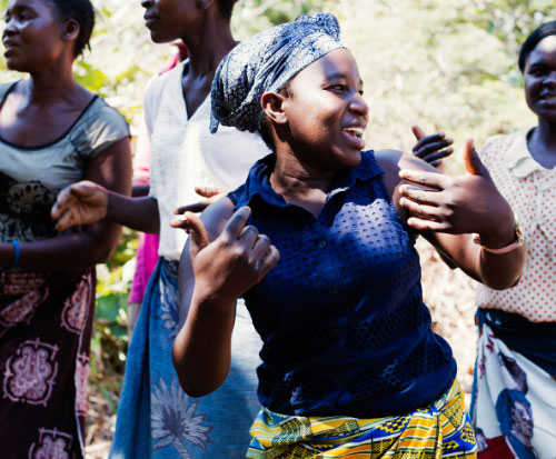 A happy Malawian lady dances with her thumbs up