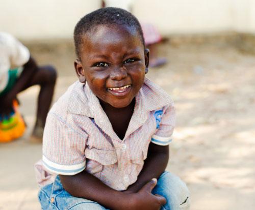 A little boy sits smiling outside preschool in Malawi