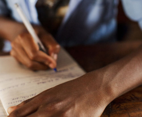 A student writes in class in Malawi