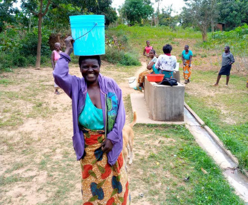 A woman carries water on her head in Malawi