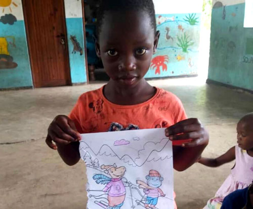 A little girl at preschool in Malawi shows a finished drawing