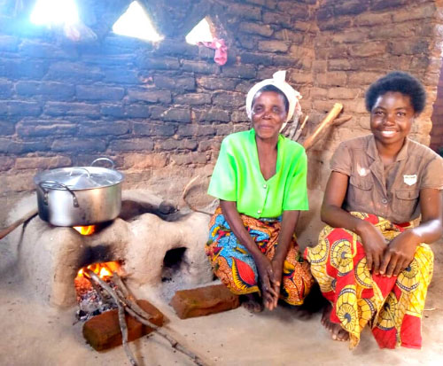 Catherine sits with her mother in law by their fuel efficient cookstove in Malawi