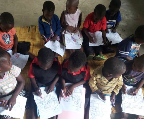 Children at preschool in Malawi colour in pictures