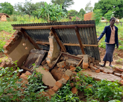 One of our preschool teachers stands next to the toilet which collapsed due to heavy rain