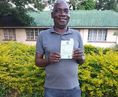 Force shows his coronavirus vaccination passport in Malawi
