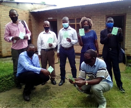 Teachers from Mwaya Primary School show their coronavirus vaccination passport in Malawi
