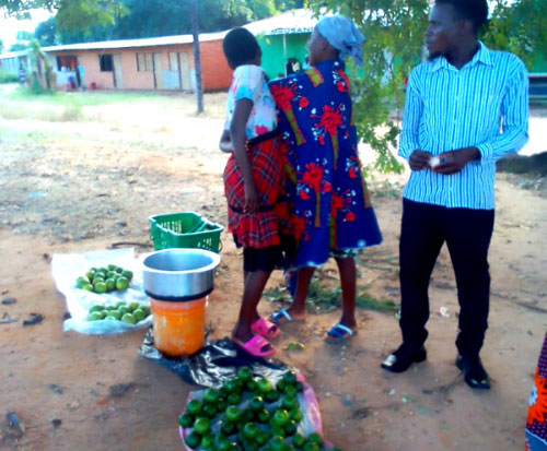 A family selling fruit at a market in Malawi