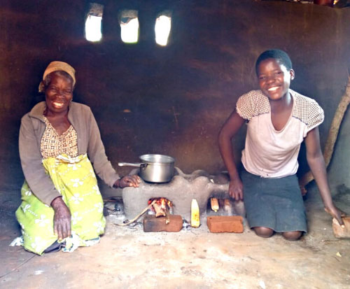 Joyce and Chimwemwe cook together on their fuel efficient cookstove in Malawi