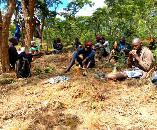 Kunene Forest Conservation Committee take a rest after creating firebreaks in forest in Malawi