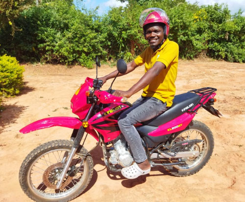 Francis sits on his new motorbike in Malawi