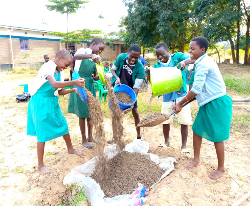 Students at Mwaya Primary School get hands on mixing manure for their fruit trees in Malawi